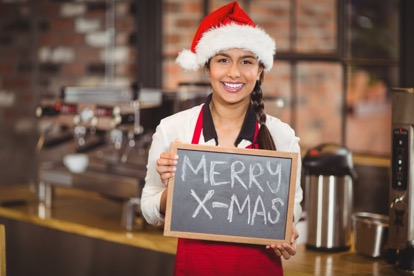 Portrait of a waitress with a chalkboard merry x-mas at the coffee shop