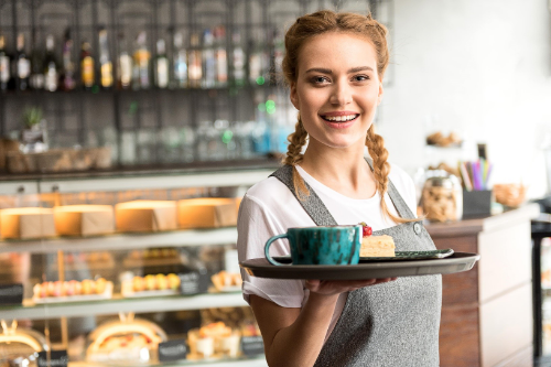 A waitress holding a tray and smiling