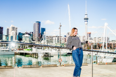 Girl leaning against railing in Auckland Viaduct with Sky Tower in background
