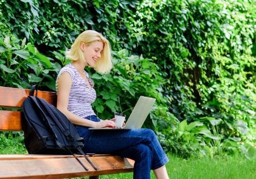 Girl sitting at her laptop studying outdoors in the sun
