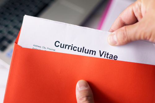 Hand pulling a curriculum vitae out of a folder.