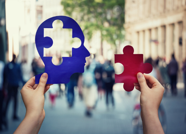 Two hands: one holding up a person cut-out lacking a jigsaw piece, the other holding up the jigsaw piece, learning concept