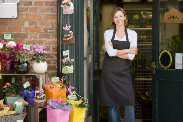 Woman florist standing outside of her small business shop