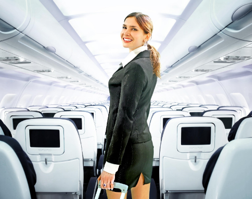A flight attendant smiling in the centre of a plane