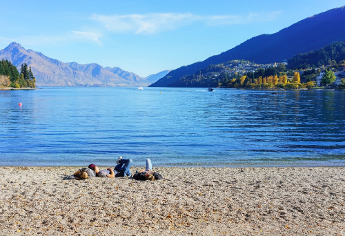 People relaxing on the beach of Lake Wakatipu in the sunny day Queenstown South Island of New Zealand